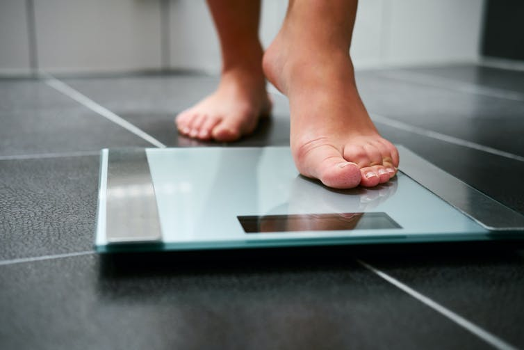 A person steps onto bathroom scales.