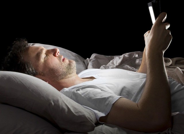 Man laying in bed on phone