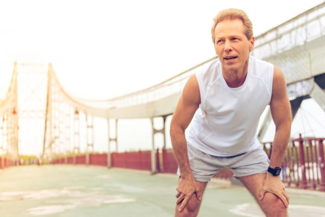 middle aged man in sports uniform is respiring deeply and leaning on his knees during morning run