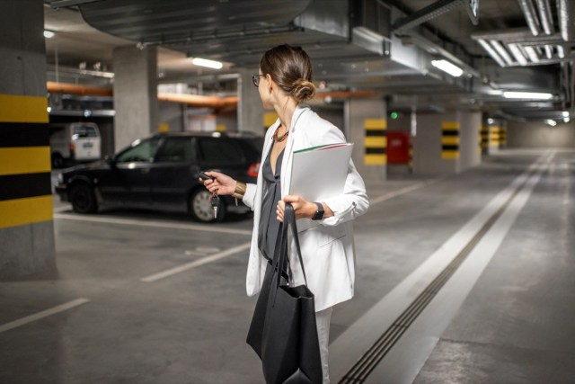 Young business woman walking with car keys in the underground parking of the new residential building - Image