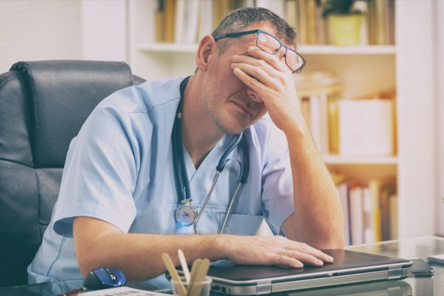 Overworked doctor sitting in his office