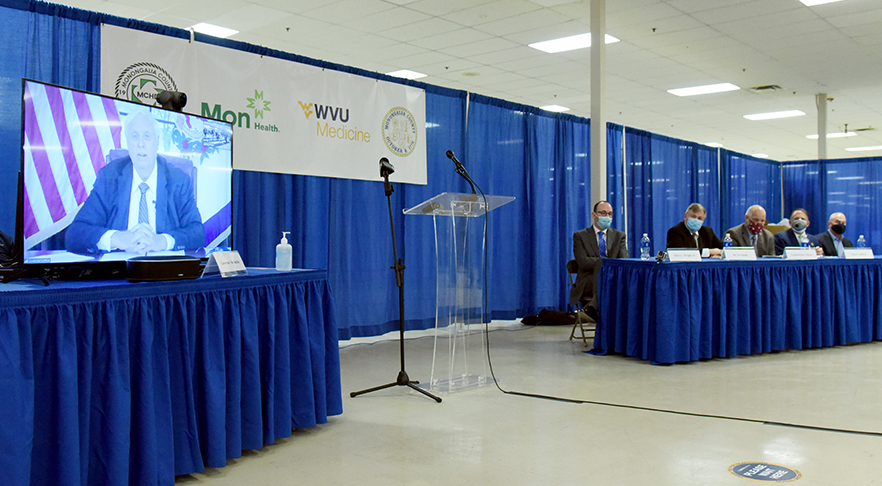 """Gov. Jim Justice (on screen) speaks during the press conference announcing Monongalia County, the Mon Health Department, Mon Health System, and WVU Medicine forming a partnership to provide COVID-19 vaccines to the community. Seated at the table (from left to right) are Albert L. Wright, Jr., president and CEO of the West Virginia University Health System; Lee B. Smith, M.D., J.D., executive director of the Mon County Health Department; Monongalia County Commissioner Sean P. Sikora; David S. Goldberg, president and CEO of the Mon Health System; and Clay B. Marsh, M.D., vice president and executive dean of WVU Health Sciences and """"COVID-19 czar"""" for the State of West Virginia."""