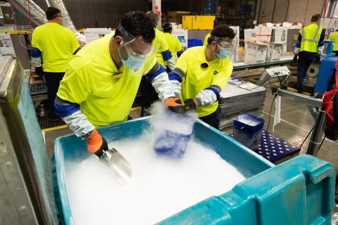 Workers at Pfizer's manufacturing site in Kalamazoo, Mich., fill buckets with dry ice that will be poured into thermal shipping containers holding the company's COVID-19 vaccine, which needs to be kept at minus-94 degrees. The Johnson & Johnson vaccine, expected to be authorized by late February, won't have that requirement.