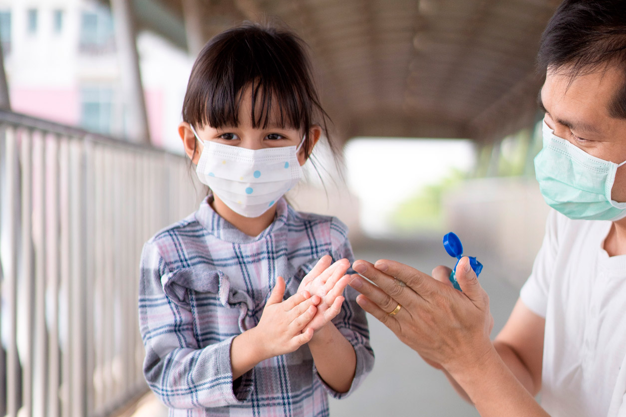 man and a girl wearing face masks share hand sanitizer